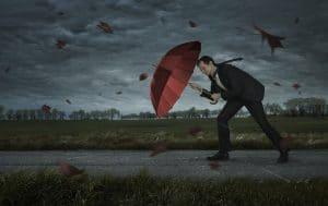 Mann mit Regenschirm im Sturm. Die Kanzlei Dierkes lässt Sie nicht im Regen stehen.