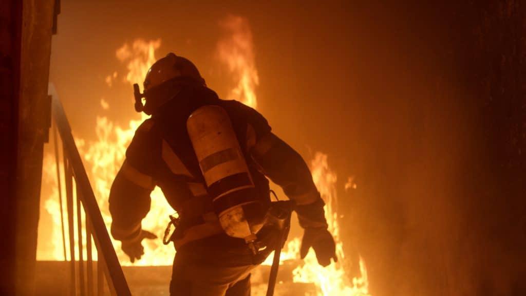 """Feuerwehrmann vor einem Feuer: Nicht immer können Feuerwehrleute helfen, wenn mal Ihre """"Hütte"""" brennt! Dann kontaktieren Sie uns!"""